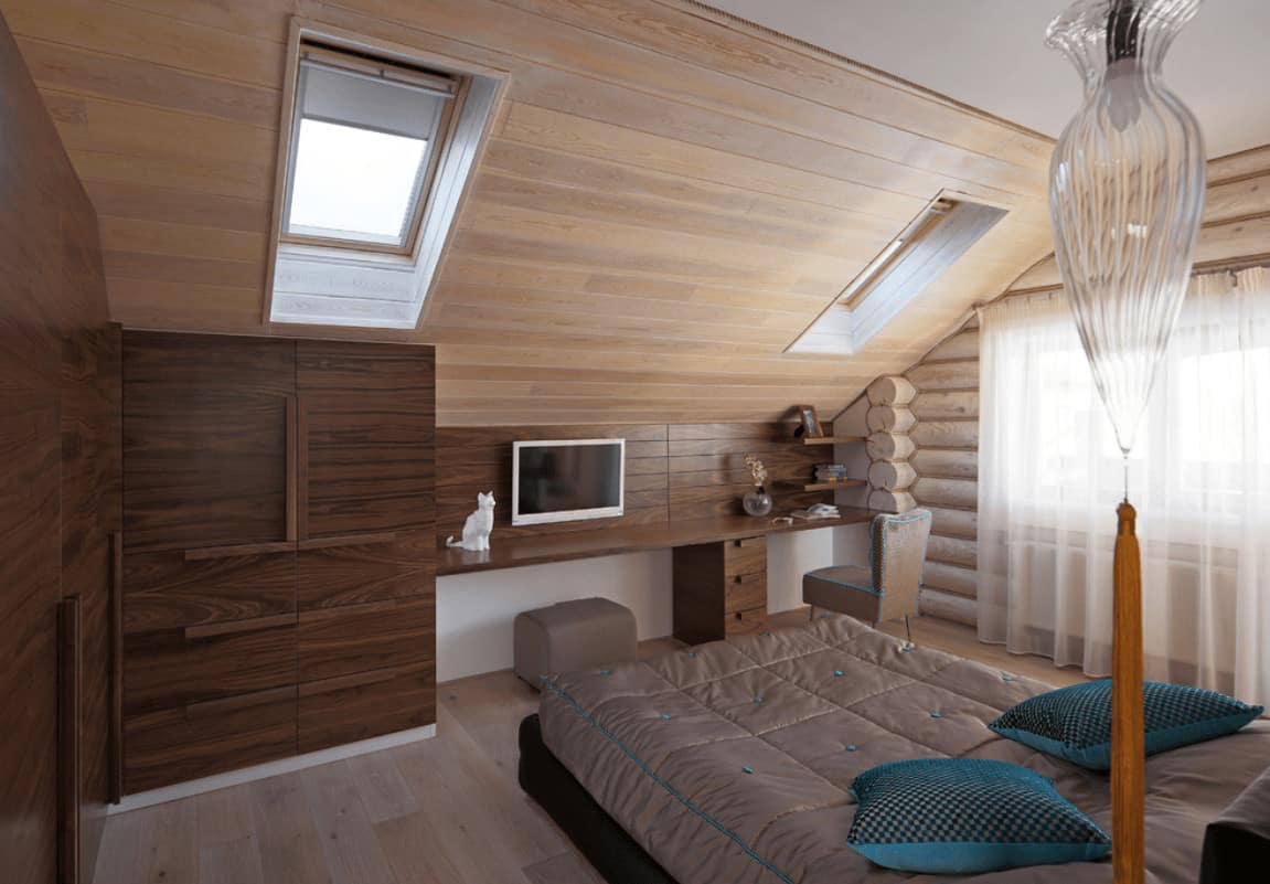 A cozy bed faces the built-in desk in this master bedroom with floor to ceiling cabinets and a vaulted wall clad in light wood planks and fitted with skylight windows.