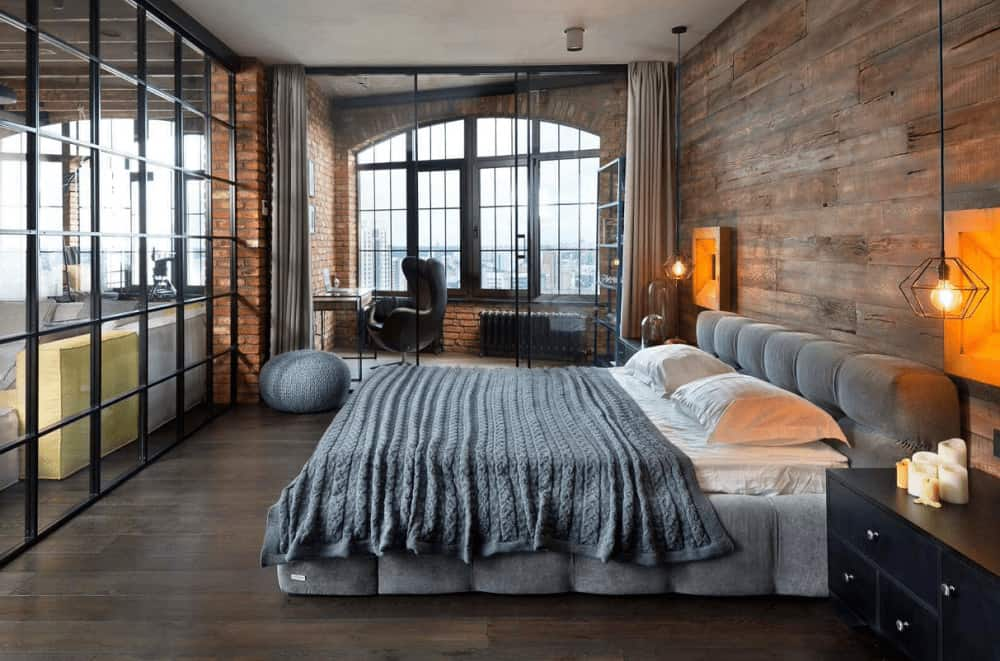 Industrial master bedroom illuminated by geometric pendant lights that hung over the black nightstands flanking a gray tufted bed. It has wide plank flooring and a glazed door that leads to the office area.
