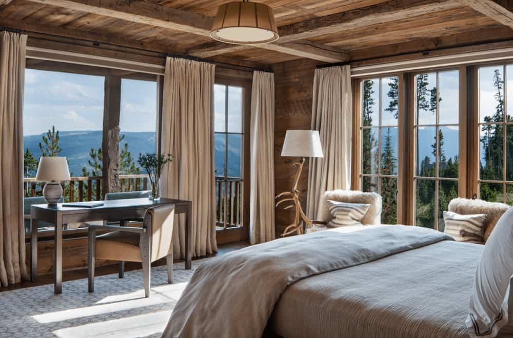 Brown master bedroom surrounded with floor to ceiling windows that overlook the stunning mountain. It has a wooden desk and a cozy bed illuminated by a pendant light.