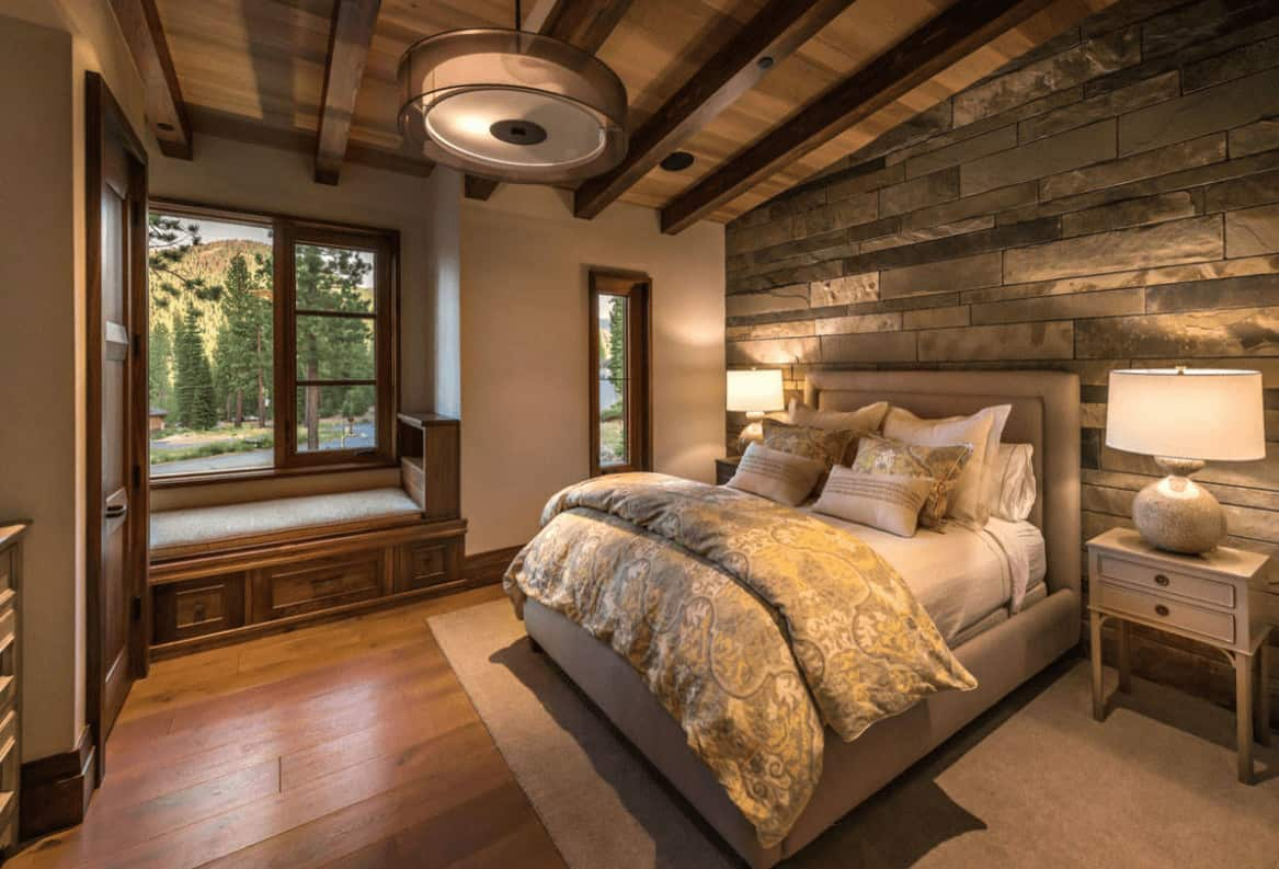 A stone accent wall adds texture in this master bedroom with a window seat nook and beige upholstered bed lighted by a pair of table lamps along with a drum pendant light.