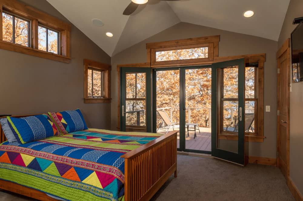 A wooden bed dressed in brightly multi-colored bedding stands out in this brown master bedroom with carpet flooring and glass double door that leads out to the balcony.