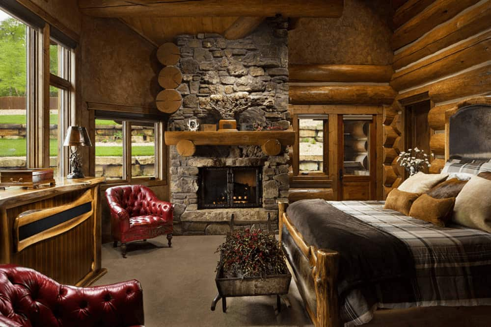 Fluffy earthy pillows lay on the cozy bed in this master bedroom boasting red chesterfield chairs and a stone fireplace lined with a wooden mantel.