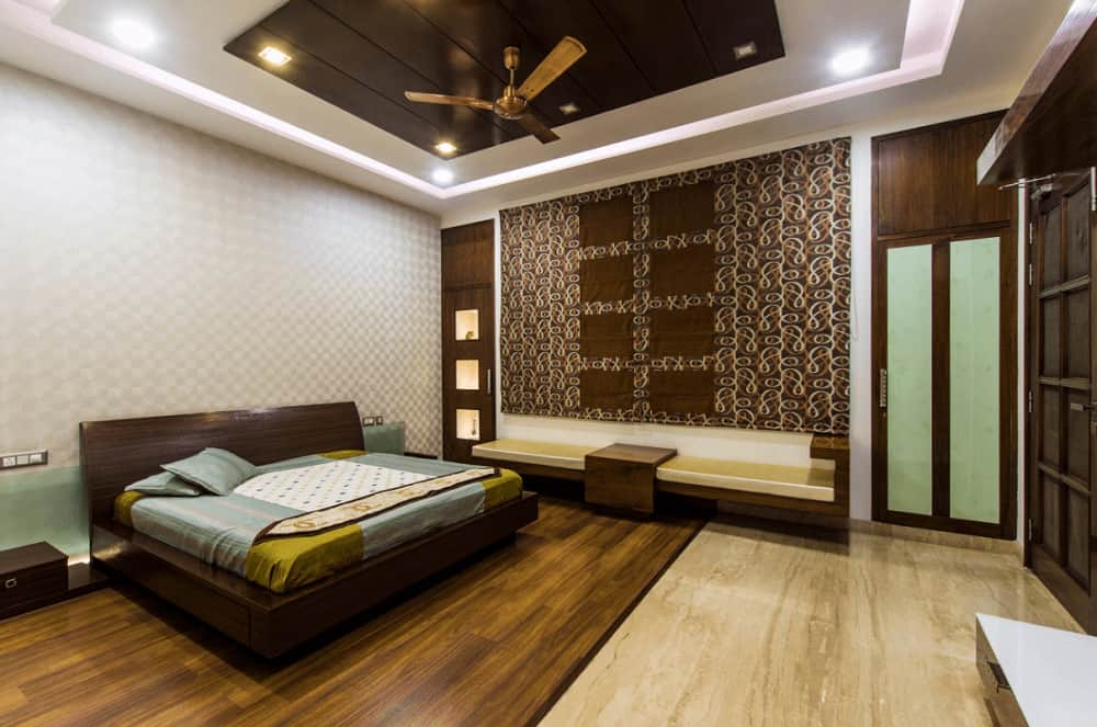 This master bedroom offers a platform bed and a sleek seat on the side accented by a large patterned tapestry. It has hardwood flooring and tray ceiling mounted with a bronze fan.