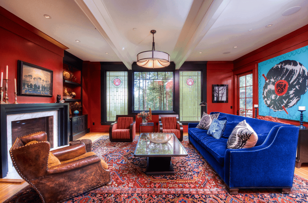 Large blue artwork and gorgeous velvet sofa stand out in this red living room showcasing cozy seats and sleek coffee table illuminated by a drum pendant and recessed ceiling lights. There's a brick fireplace on the side framed with white marble surround and black mantel.