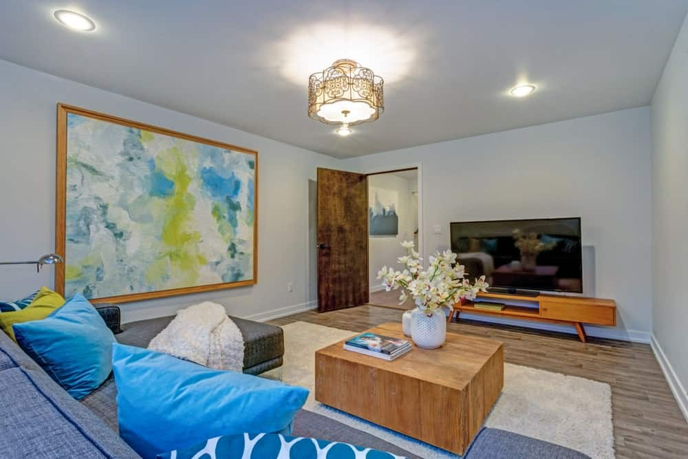 Cozy living room decorated with a large abstract painting and a gorgeous semi-flush mount light that hung over the wooden coffee table. It has a flat-screen TV and gray sofa filled with blue pillows.