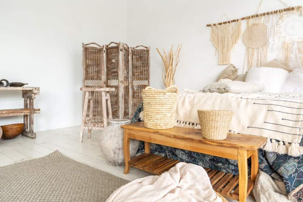 Spacieuse chambre des maîtres avec grand lit élégant, mobilier rustique et design entouré de murs et de plafonds blancs.