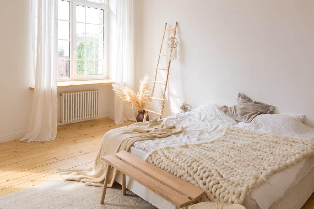 Un coup concentré sur le grand lit de cette chambre principale posé sur le parquet.  La fenêtre en verre sur le côté présente de beaux rideaux blancs.