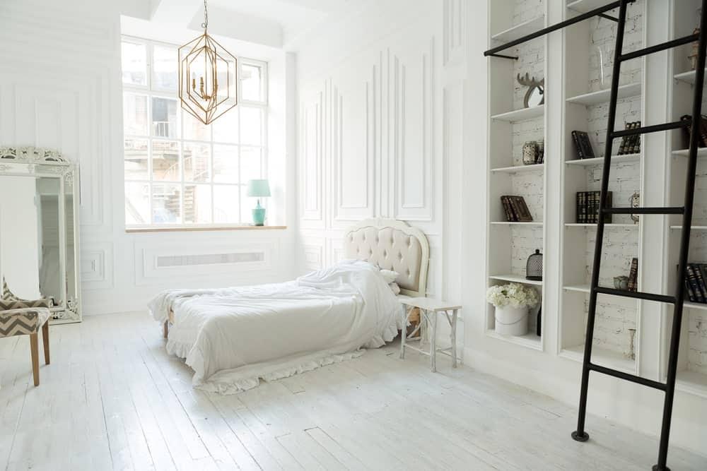 Grande chambre des maîtres avec un haut plafond et des murs blancs.  La chambre a une configuration de lit charmante éclairée par un magnifique plafonnier.  La salle offre également des étagères intégrées.