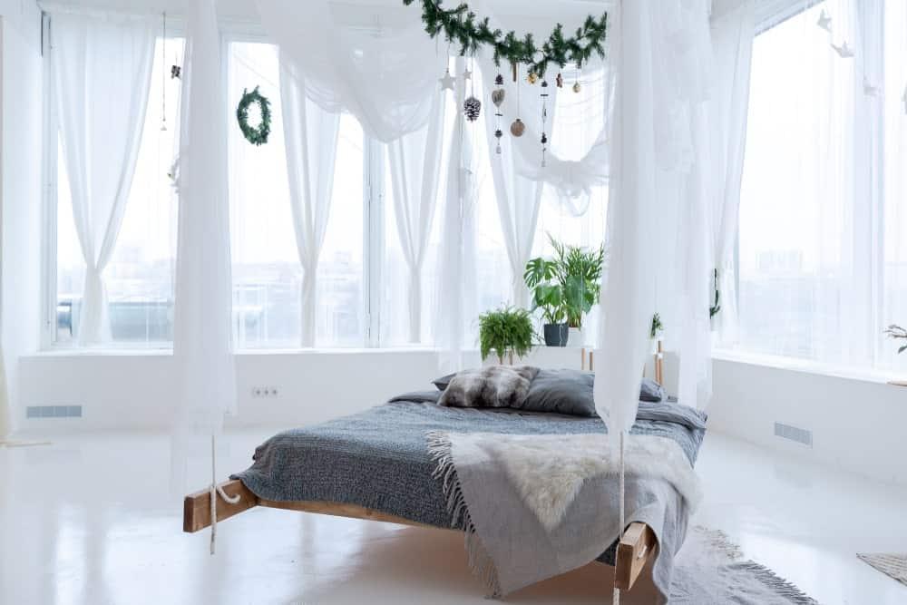 Un tir concentré sur le magnifique lit de cette chambre principale avec des plantes d'intérieur, entouré de murs et de sols blancs, ainsi que de rideaux blancs.