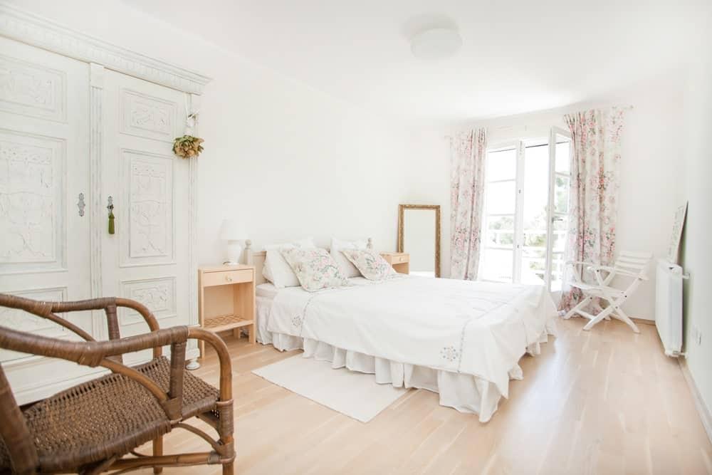 Chambre de style cottage avec rideaux de fleurs, portes françaises menant au balcon et commode shabby chic.