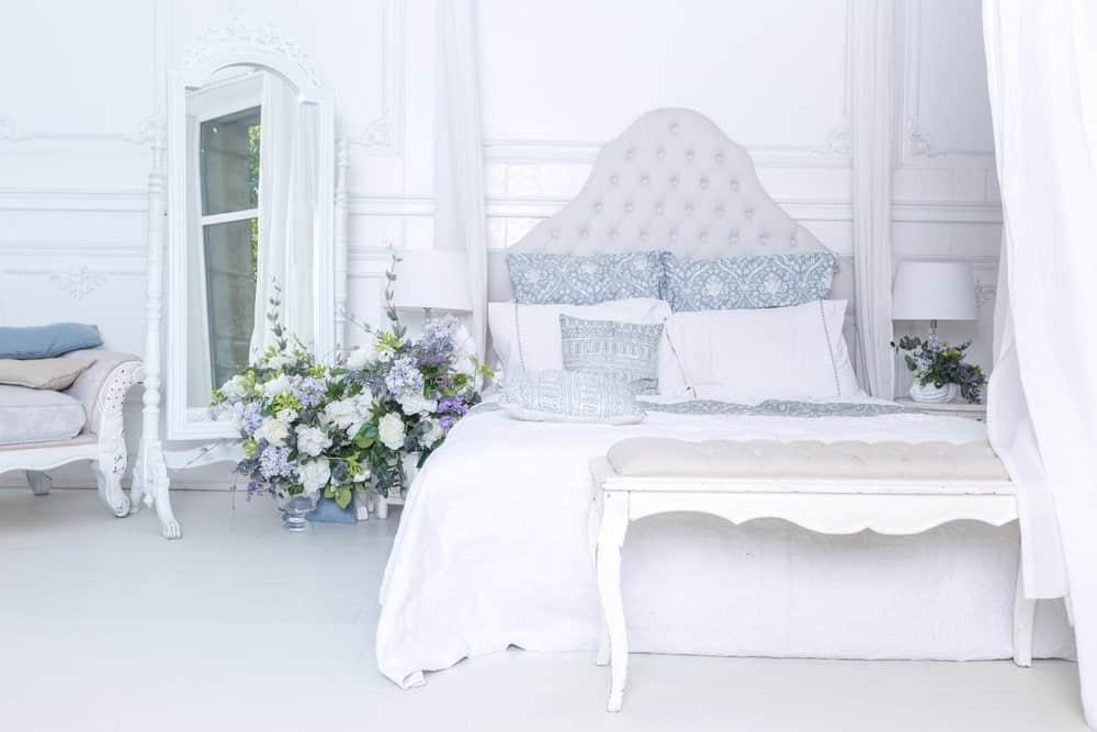 Grande chambre des maîtres avec une magnifique configuration de lit avec de belles fleurs sur le côté, éclairée par des lampes de table et entourée de murs et de sols blancs.