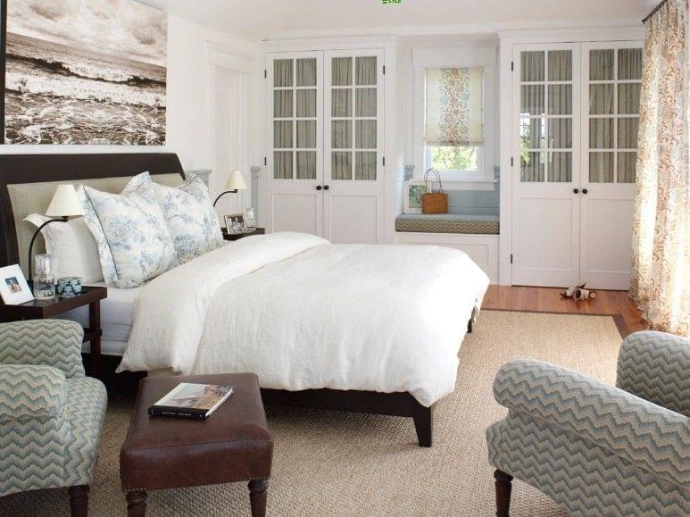 La chambre principale comprend un grand lit confortable et un coin salon avec deux belles chaises sur le côté.