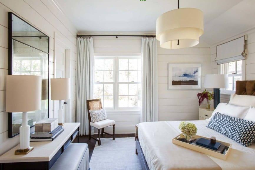 Spacieuse chambre principale avec un grand lit élégant et un bureau intégré éclairé par deux lampes de table.  La chambre dispose également d'un charmant plafonnier.