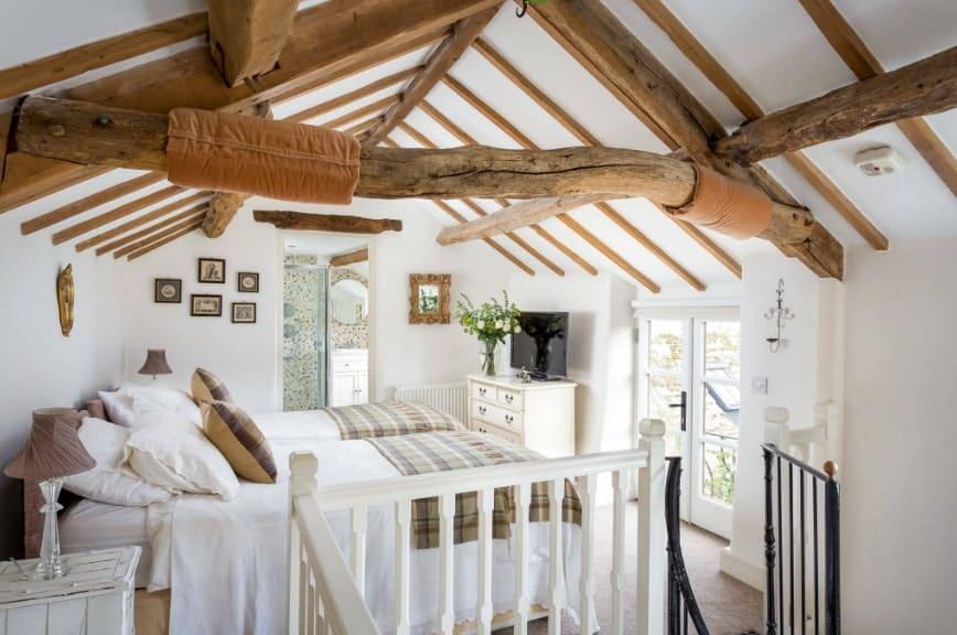 Grande chambre des maîtres avec des murs blancs et un plafond avec poutres apparentes.  La chambre dispose de deux lits avec une télévision au-dessus du meuble.