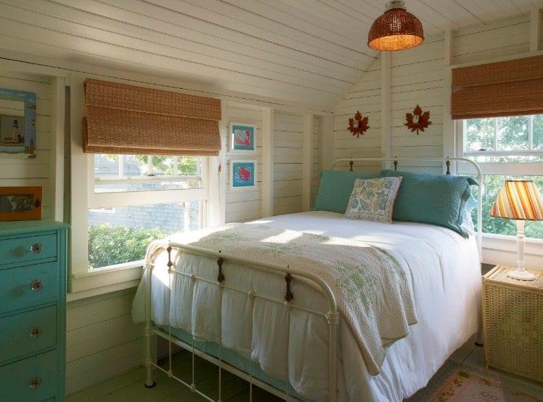 Un tir concentré sur le lit confortable de cette chambre principale entouré de murs blancs, de parquet et d'un plafond en bois.