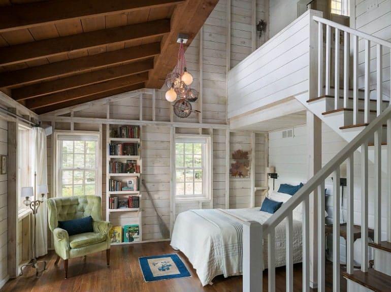 Cette chambre principale dispose d'un plafond en bois, de murs en bois et de parquet.  Il a un escalier menant à la salle de bain.
