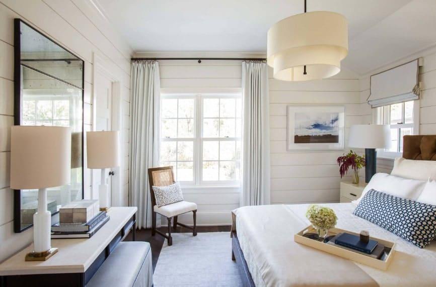 La chambre principale dispose d'un lit élégant et d'un bureau intégré éclairé par des lampes de table.  La chambre dispose également d'un charmant plafonnier.