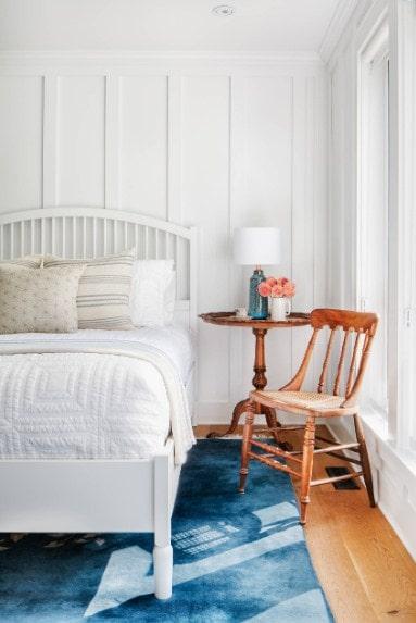 Cette chambre principale offre un grand lit blanc assorti aux murs blancs et au plafond blanc.  Le plancher de bois franc est surmonté d'un élégant tapis bleu.