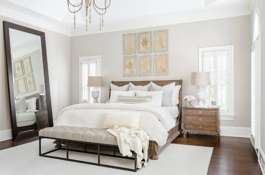 Spacieuse chambre principale avec un grand lit avec des tables de chevet rustiques surmontées de lampes de table chics.  La salle dispose de parquet en bois dur surmonté d'un tapis blanc.