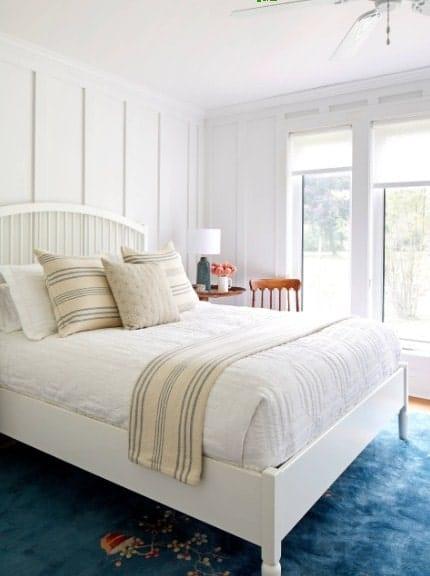 Regardez de plus près le lit blanc de cette chambre principale posé sur un élégant tapis bleu entouré de murs et de plafonds blancs.