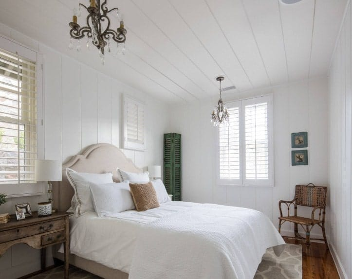 Cette chambre principale comprend un lit élégant éclairé par deux magnifiques lustres et est entourée de murs et d'un plafond en bois blanc.