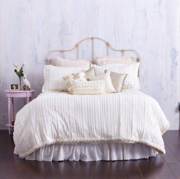 Un plan rapproché à la belle configuration du lit de cette chambre principale avec une petite table d'appoint rose.  La chambre dispose également de parquet.