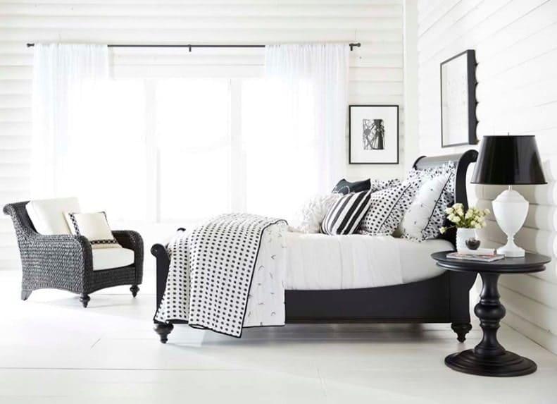 Chambre des maîtres lumineuse avec un accent noir.  Il est doté d'un sol et de murs blancs, d'un cadre de lit noir et d'autres meubles au fini noir.