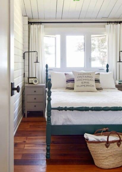 Un coup porté au lit de cette chambre principale près des fenêtres.  La chambre est dotée de parquet et d'un plafond en bois.