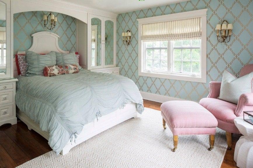 Chambre des maîtres avec d'élégants murs verts éclairés par des appliques murales.  La chambre offre un grand lit élégant avec une chaise rose avec un repose-pieds sur le côté.  Le plancher de bois franc est surmonté d'un tapis blanc.