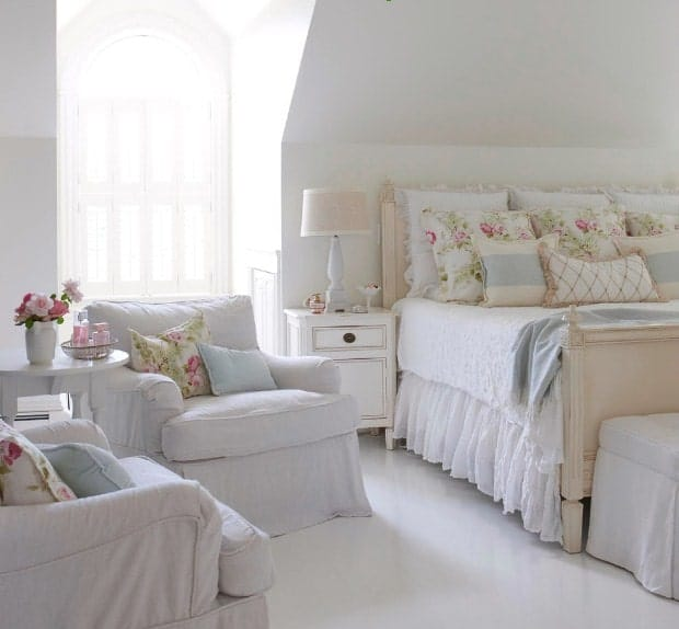 Chambre à coucher principale blanche avec sol et murs blancs.  La chambre offre un grand lit magnifique ainsi que deux sièges blancs sur le côté et une petite table centrale.