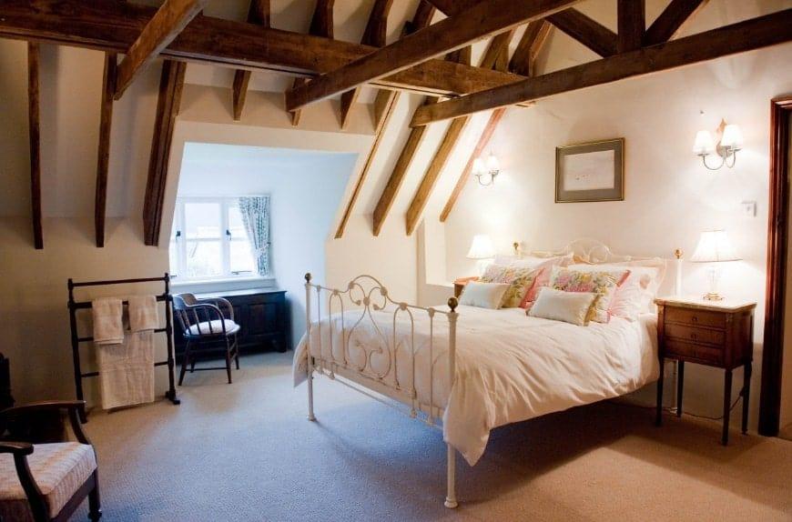 Grande chambre des maîtres avec moquette et plafond aux poutres apparentes.  La chambre offre un joli lit blanc éclairé par des appliques murales.