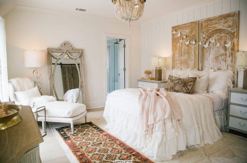 La chambre principale dispose d'un lit élégant éclairé par deux lampes de table élégantes et un lustre glamour.  La chambre a aussi sa propre salle de bain.