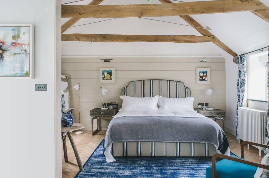 Grande chambre principale dotée d'un lit élégant posé sur un élégant tapis bleu recouvrant le parquet en bois dur à chevrons.