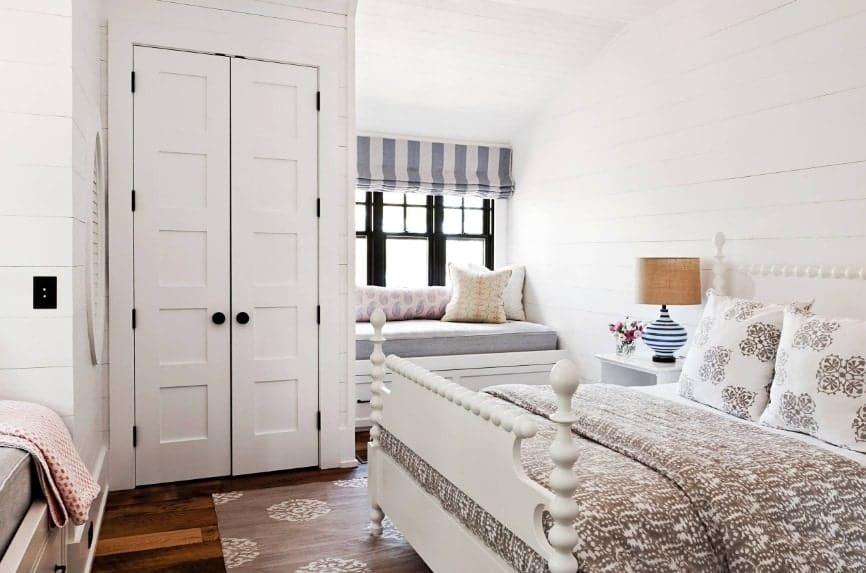 Chambre à coucher principale avec plancher de bois franc, murs blancs et plafond blanc.  La chambre offre un grand lit élégant et une banquette près des fenêtres.