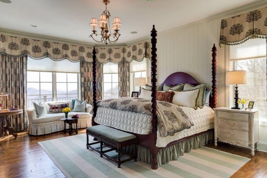 Grande chambre des maîtres avec des rideaux élégants et un magnifique lustre.  La chambre a un grand lit confortable et un beau canapé près des fenêtres.
