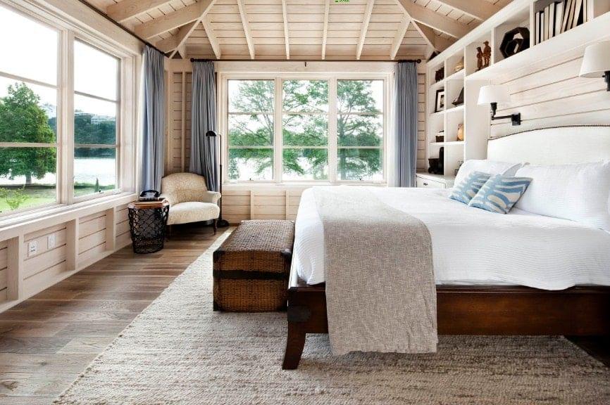 Spacieuse chambre des maîtres avec murs en bois et parquet, avec un plafond en bois.  La chambre a un grand lit et plusieurs étagères intégrées.