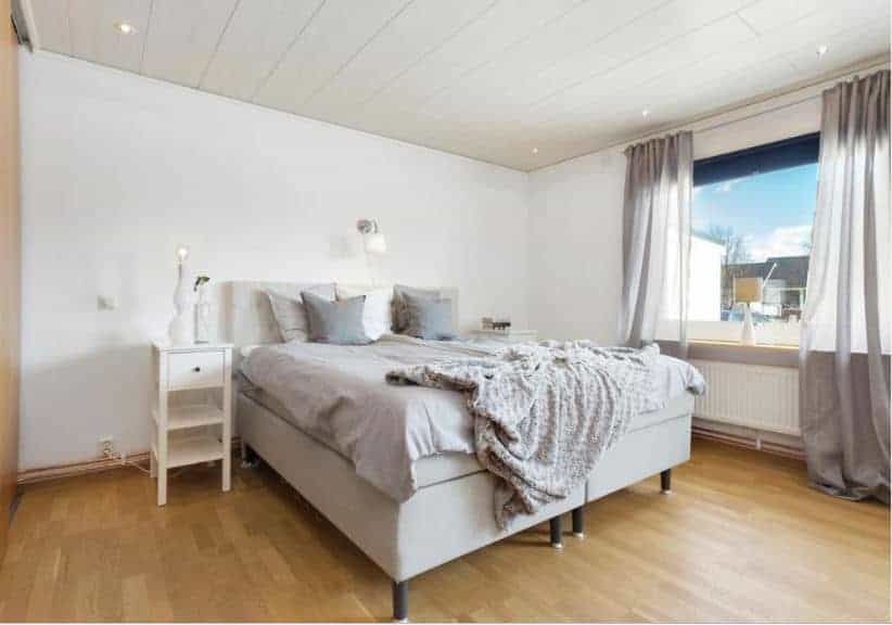 The light gray platform bed stands out against the white walls of this Scandinavian-Style bedroom. The wall above the bed has a wall-mounted modern lamp for late-night reading. This matches with the white wooden bedside tables.