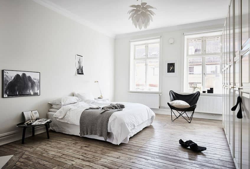 This is a bright and airy Scandinavian-Style bedroom with hardwood floors illuminated by the pair of tall windows dominating one wall. The white sheets of the cottage-style bed are contrasted with a dark wooden bedside table and wall-mounted black and white photo.