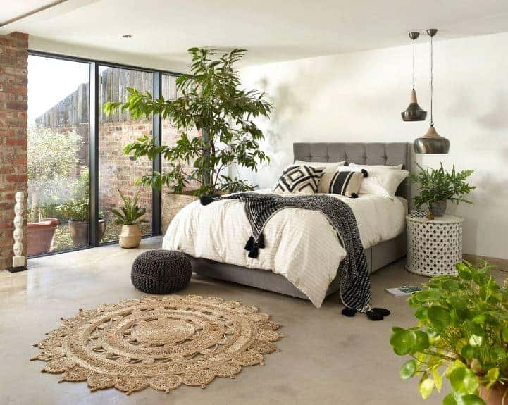 This bedroom has white walls and a white ceiling that serve as a nice background for the plant accents that match with the plants outside the glass floor-to-ceiling window. This contrasts well with the dark gray cushions of the traditional bed.