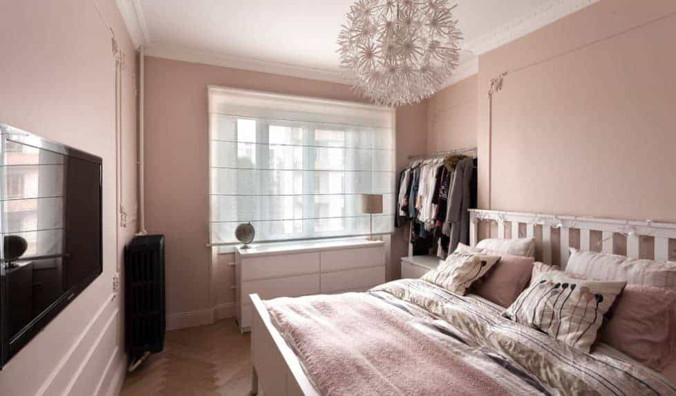 This is a distinctly chic Scandinavian-style room with its pink walls and bedsheets paired with spherical pendant light with dandelion designs. This theme is amplified by the string lights on the wooden headboard of the mission type bed.