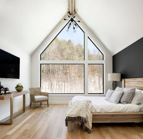 The massive glass window of this Scandinavian-Style bedroom follows the lay of the high white cathedral ceiling with a single exposed wooden beam in the middle that supports a modern chandelier. The wall behind the wooden traditional bed is painted dark gray contrasting the other walls.