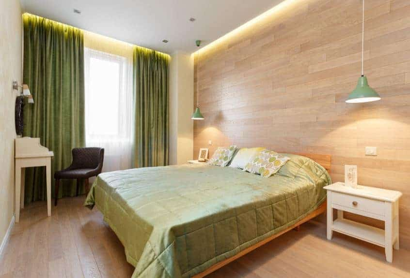 The chic greenish sheets of the traditional wooden bed match well with the green curtains of the tall windows. These green hues are a perfect contrast for the white ceiling, wooden walls, and hardwood flooring.