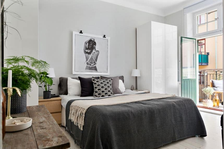 The natural light coming in from the French glass doors and windows above it illuminate the white walls, ceiling and the sleek white cabinet beside the bed. There is a lovely framed photo of a woman mounted above the bed with gray sheets.