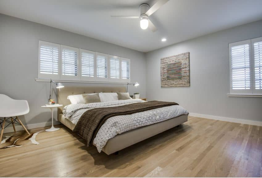 The hardwood flooring is illuminated by the pin lights and ceiling fan with semi-flush light mounted on the white ceiling. There is a row of small shuttered windows above the gray cushioned headboard that is flanked by modern table lamps on white bedside tables.