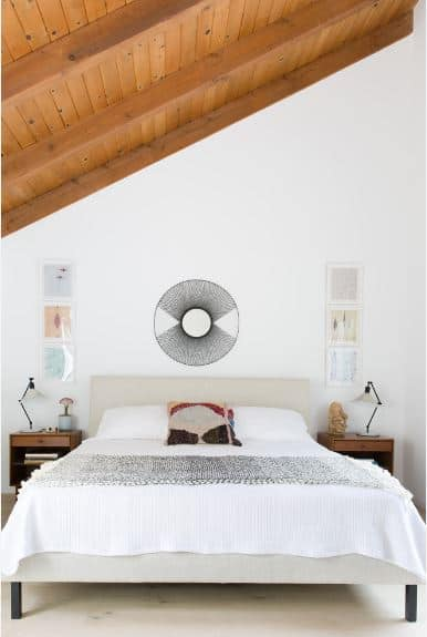 The shiplap wooden ceiling of this Scandinavian-Style bedroom has exposed wooden beams that contrast with the white walls and white flooring. The light gray hue of the headboard molds into the white wall above it and accented with a circular artwork.