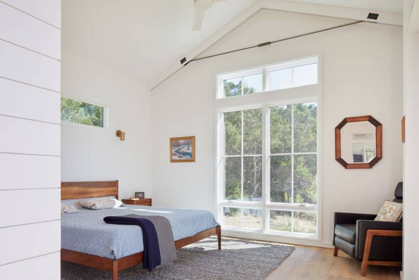 This is an airy Scandinavian-Style room with an abundance of natural light coming from the tall glass window that almost goes up to the white cathedral ceiling. This illuminates the wooden traditional bed that has light blue sheets contrasting the gray area rug over the hardwood flooring.