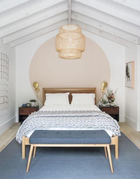 This is a cozy alcove Scandinavian-Style bedroom with a pedant light covered in woven wicker hanging from the white cathedral ceiling that has exposed wooden beams. The wooden headboard of the bed is against the white wall painted with a huge beige circle that matches the wall-mounted painting.