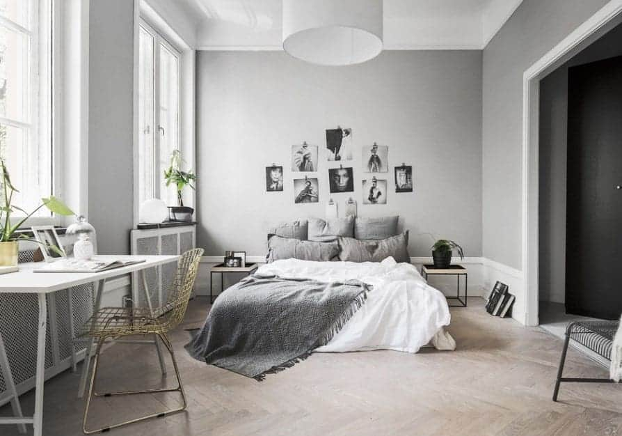 Large Scandinavian-Style primary bedroom featuring stylish gray walls with attractive wall decors and herringbone hardwood flooring.