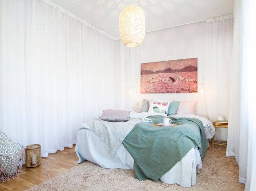 Small Scandinavian-Style primary bedroom featuring lovely white window curtains and a charming pendant lighting.