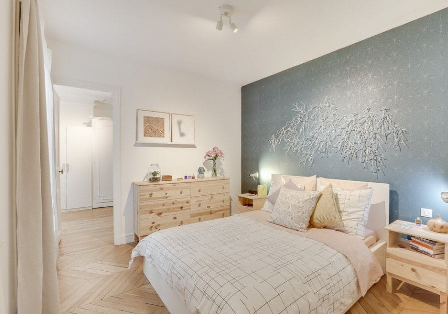 A Scandinavian-Style primary bedroom featuring a very stylish wall with bright and cute decorations along with the room's charming herringbone hardwood flooring.